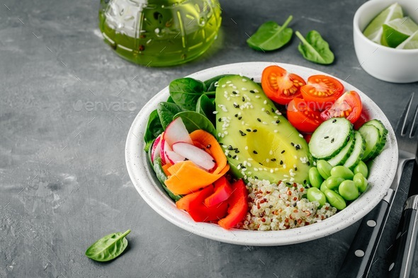 Buddha bowl with Avocado, quinoa, tomatoes, cucumbers, spinach, carrots, paprika and edamame - Stock Photo - Images