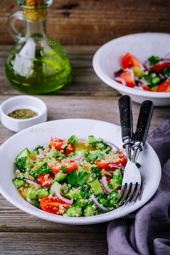 Quinoa Tabbouleh salad bowl with cucumbers, tomatoes, red onions and parsley - Stock Photo - Images