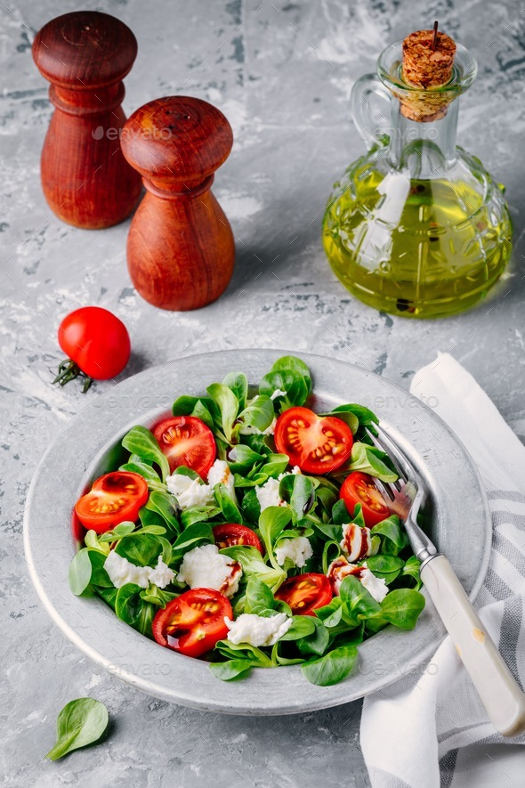 fresh salad bowl with green leaves, mozzarella, tomatoes and balsamic sauce - Stock Photo - Images