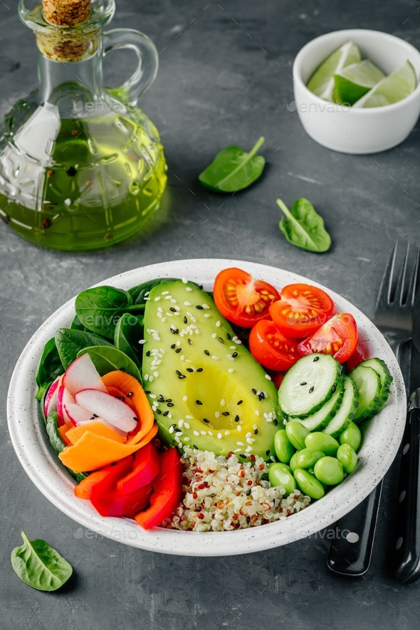Buddha bowl. Avocado, quinoa, tomatoes, cucumbers, radishes, spinach, carrots, paprika and edamame. - Stock Photo - Images