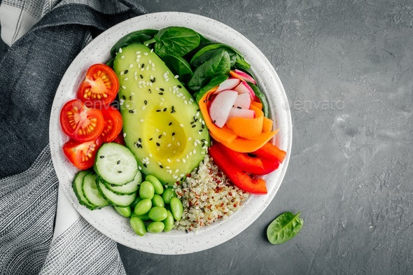 Healthy Buddha bowl. Avocado, quinoa, tomatoes, cucumbers, radishes, spinach, carrots and edamame - Stock Photo - Images