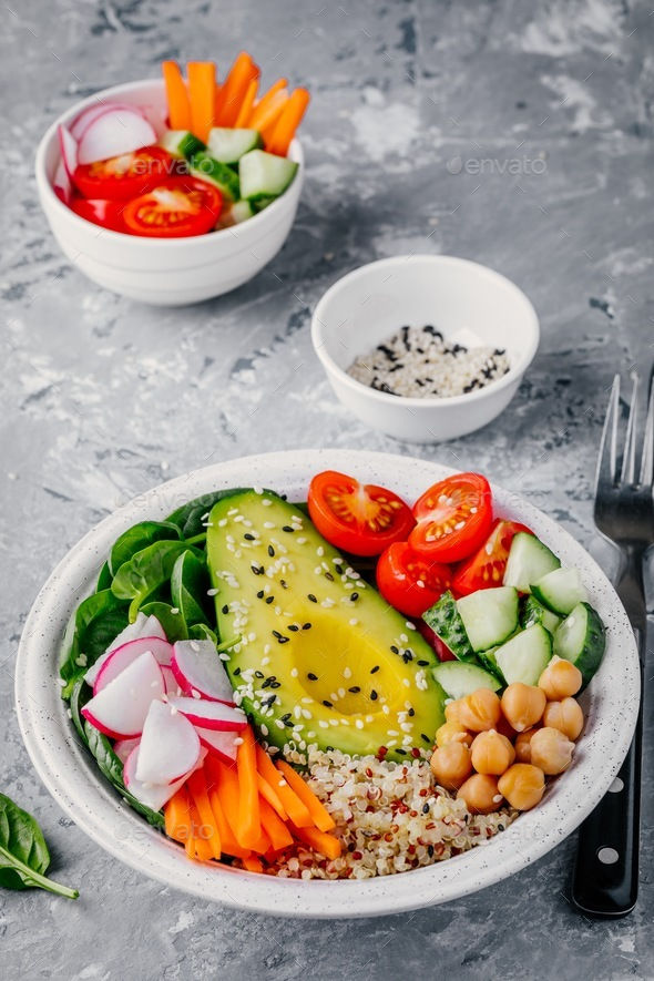 buddha bowl with quinoa, spinach, avocado, cucumbers, tomatoes, carrots, radishes, chickpeas - Stock Photo - Images