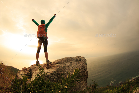 Happy on sunrise seaside cliff edge - Stock Photo - Images