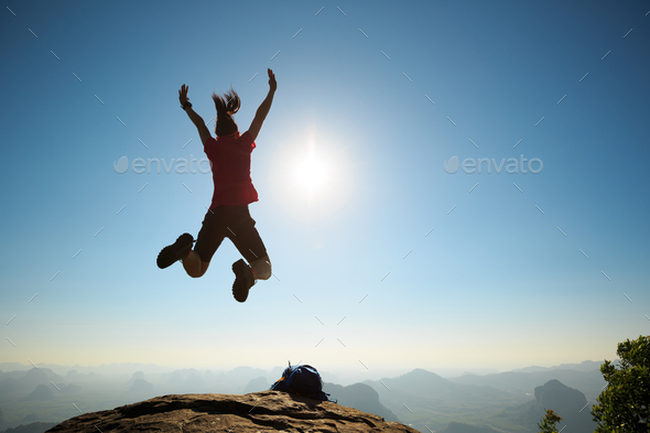 Jumping on sunrise mountain top - Stock Photo - Images