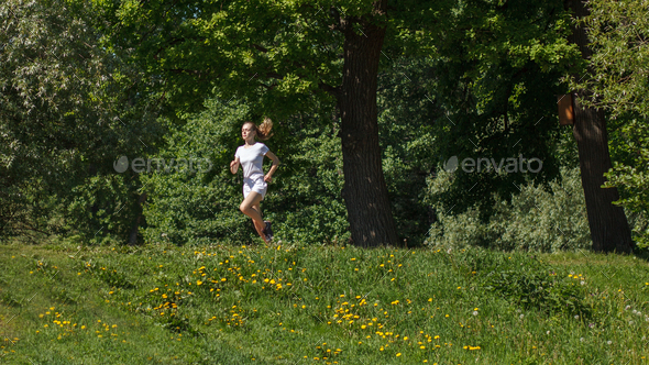 sporty woman running in summer forest - Stock Photo - Images