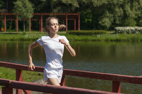 sporty woman running on wooden bridge - Stock Photo - Images