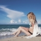 A Girl Sits on the Sand and Sunbathes - VideoHive Item for Sale