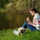 Relax with Your Favorite Dog in the Park. A Woman Uses a Tablet, Eats Fast Food - VideoHive Item for Sale