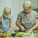 Cook Together. The Girl of 6 Years Helps Her Grandmother in the Kitchen, Watching the Salad Recipe - VideoHive Item for Sale
