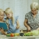 Grandmother, Mother and Granddaughter Cook Together a Salad in the Kitchen. Enjoy a Tablet, Have a - VideoHive Item for Sale