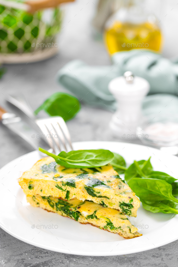 Omelet with spinach leaves. Omelette on plate, scrambled eggs - Stock Photo - Images