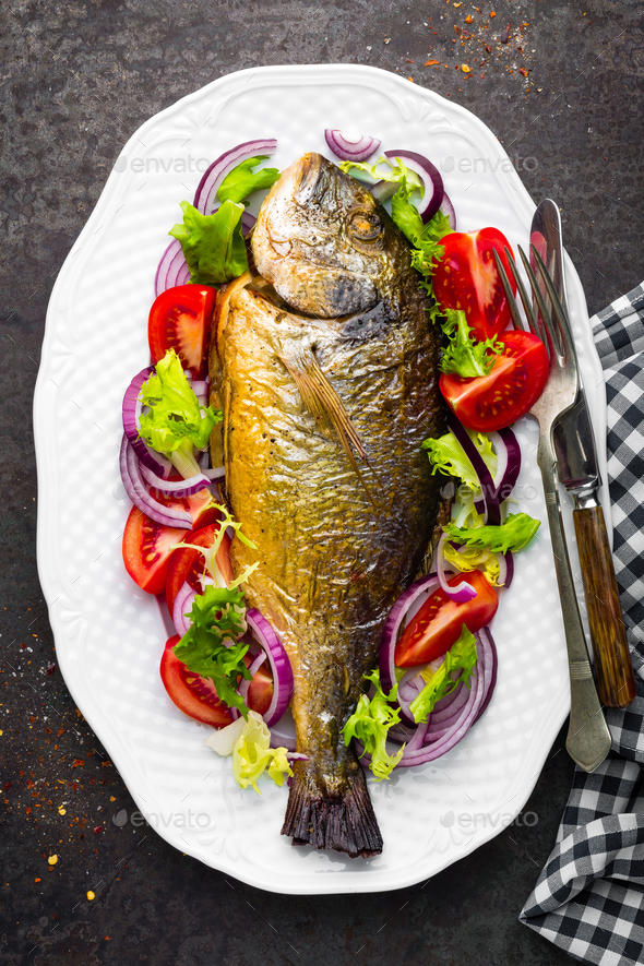 Baked fish dorado. Dorado fish oven baked and fresh vegetable salad on plate. Sea bream - Stock Photo - Images