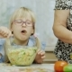 Granddaughter Visiting Grandmother. A 6 Year Old Girl Eats a Salad. Next To Her, an Elderly Woman - VideoHive Item for Sale