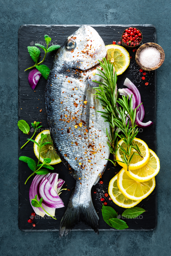 Fresh fish dorado. Rawrado fish and ingredient for cooking on board. Sea bream - Stock Photo - Images