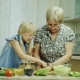 Grandmother Teaches Her Granddaughter To Prepare a Salad, Use a Tablet. Together Have a Good Time - VideoHive Item for Sale