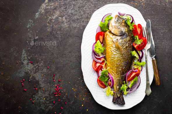 Baked fish dorado. Dorado fish oven baked and fresh vegetable salad on plate. Sea bream - Stock Photo - Images