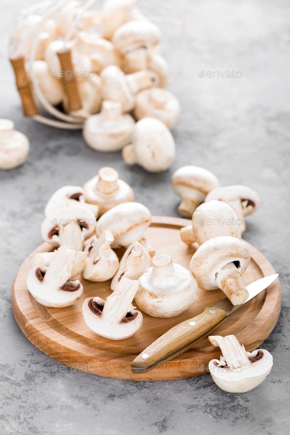 Fresh mushrooms. Raw mushrooms on wooden board. Champignons - Stock Photo - Images