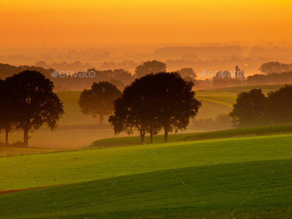 Orange sunrise over misty and hilly farmland - Stock Photo - Images
