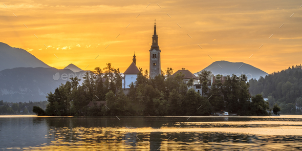 Famous landmark Island in Lake bled with church under orange mor - Stock Photo - Images