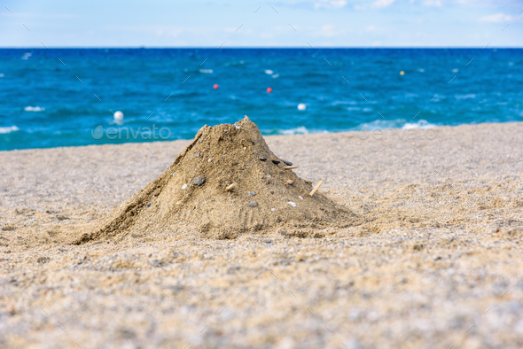 Volcano made from sand on the beach - Stock Photo - Images