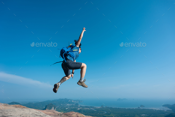 Successful hiker jumping on mountain top cliff edge - Stock Photo - Images