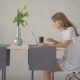 Young Girl Typing in a Laptop on Line on a Table in the Living Room at Home - VideoHive Item for Sale