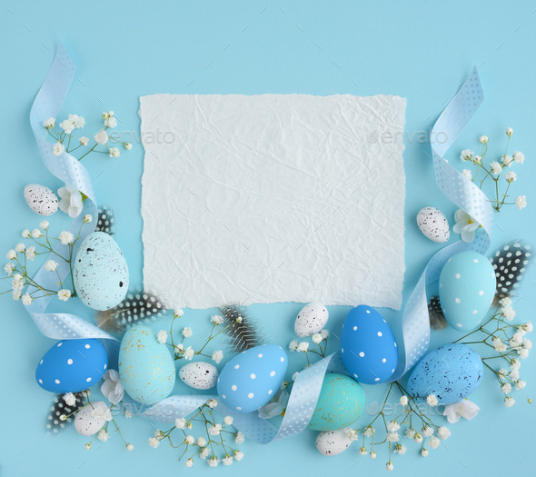 Easter eggs on a blue background. View from above, a piece of pa - Stock Photo - Images