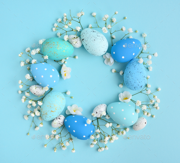 Creative Easter layout made of eggs and flowers on blue backgrou - Stock Photo - Images