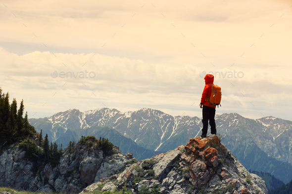 Successful hiker enjoy the view on mountain top - Stock Photo - Images