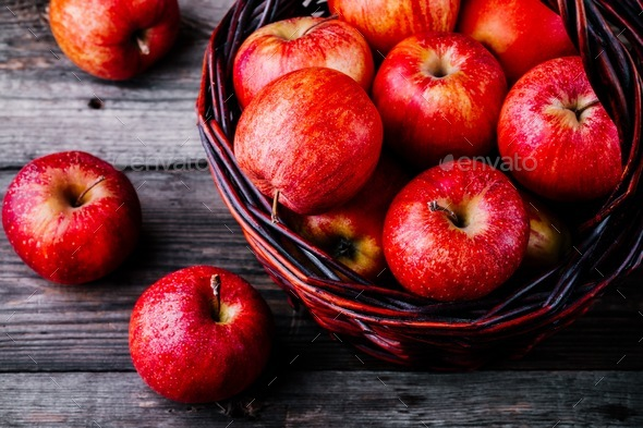 red ripe apples in a basket on a wooden background - Stock Photo - Images