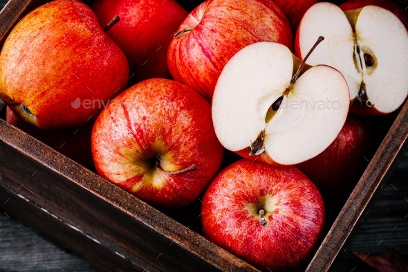 red ripe apples in a box on a wooden background - Stock Photo - Images