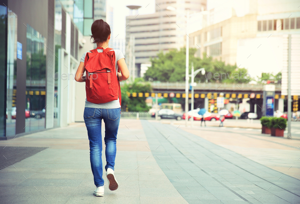 Woman with rucksack walking on street - Stock Photo - Images