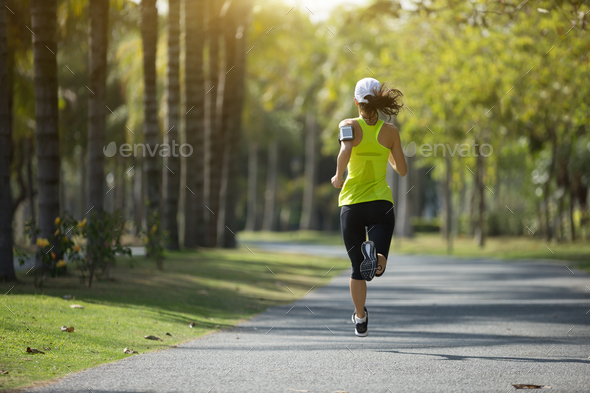 Running and listening music in park - Stock Photo - Images