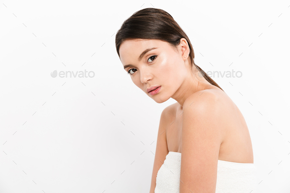 Young woman in towel looking camera isolated over white - Stock Photo - Images