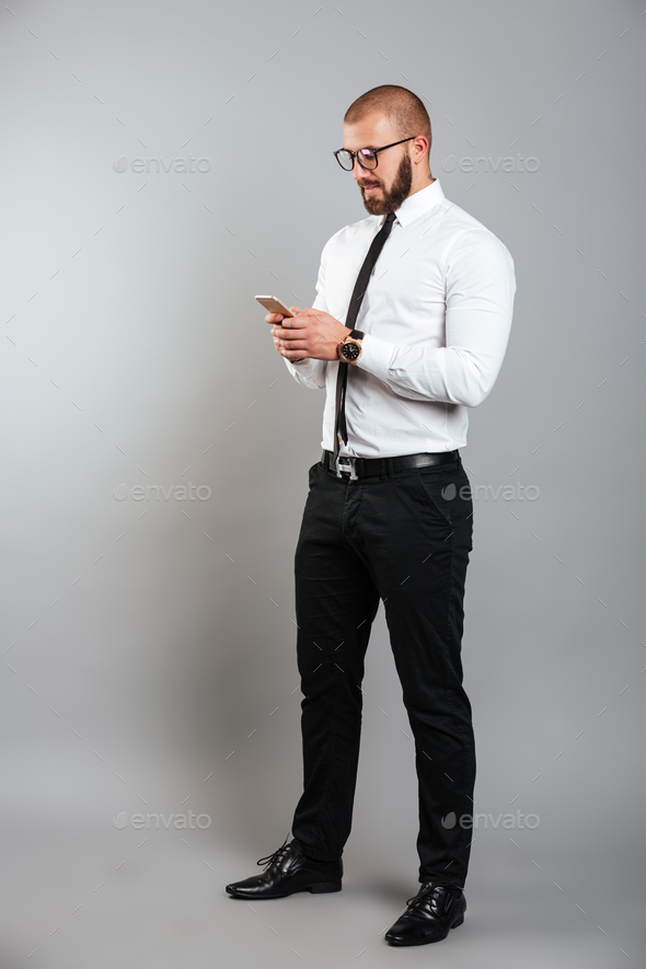 Full-length image of young unshaved man in glasses and tie chatt - Stock Photo - Images