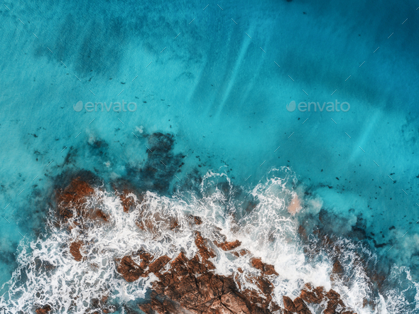 Aerial view of waves, rocks and transparent sea - Stock Photo - Images