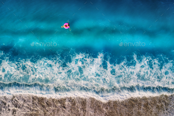 Aerial view of young woman swimming on the pink swim ring in the - Stock Photo - Images