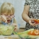 Visiting Grandmother. A 6 Year Old Girl Eats a Salad, Next To an Elderly Woman Is Cleaning an Apple - VideoHive Item for Sale