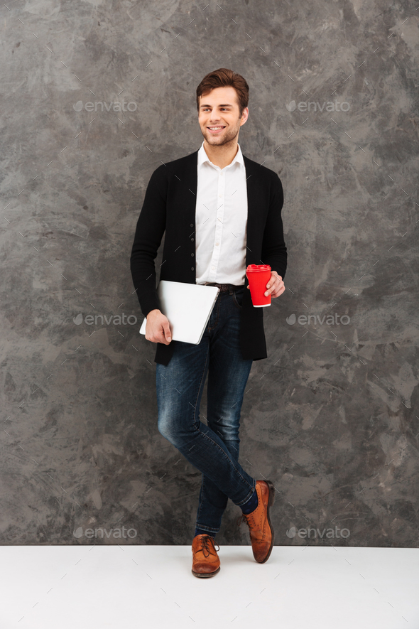Cheerful businessman holding laptop and coffee. - Stock Photo - Images