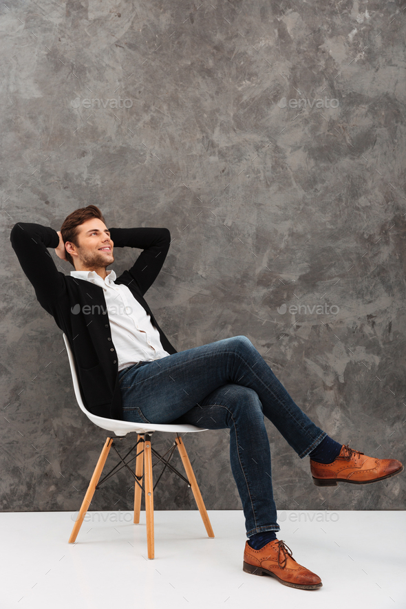 Cheerful young businessman sitting over grey wall - Stock Photo - Images