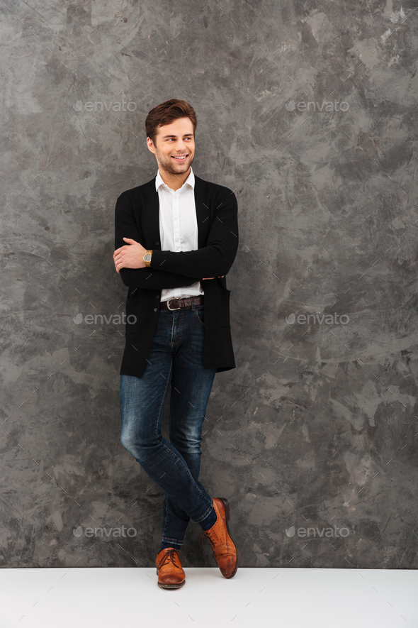 Cheerful young businessman standing over grey wall - Stock Photo - Images