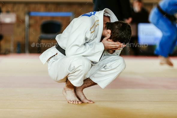 defeat judoka in white kimono - Stock Photo - Images