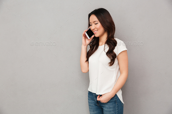 Modern asian woman in casual t-shirt and jeans having mobile cal - Stock Photo - Images