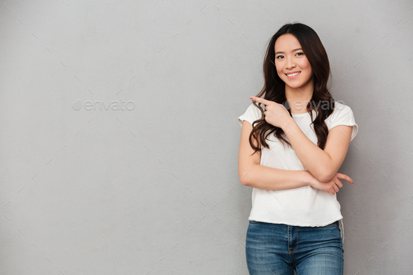 Photo of asian affable woman in casual t-shirt and jeans posing - Stock Photo - Images