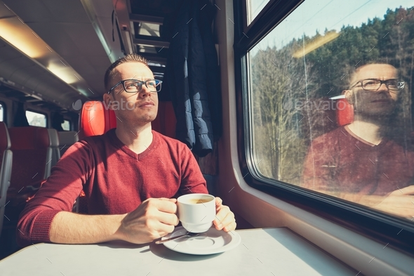 Young man traveling by train - Stock Photo - Images