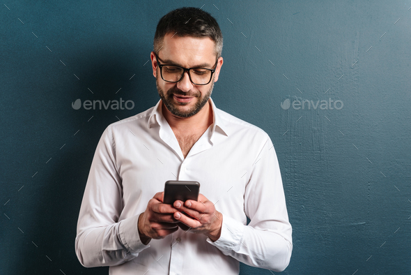 Cheerful man wearing glasses chatting by phone. - Stock Photo - Images