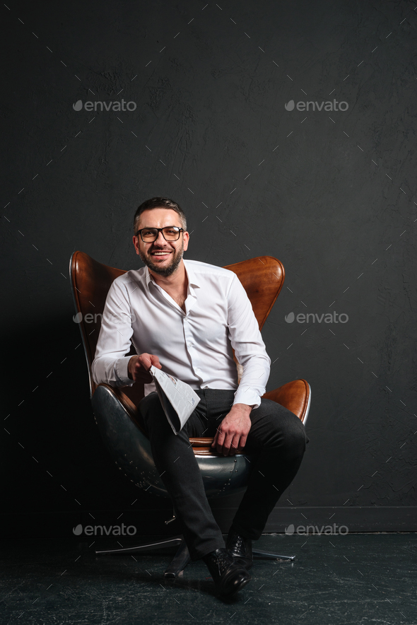 Happy businessman sitting isolated reading newspaper. - Stock Photo - Images