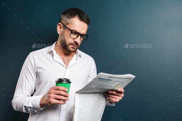 Handsome concentrated man drinking coffee reading newspaper. - Stock Photo - Images