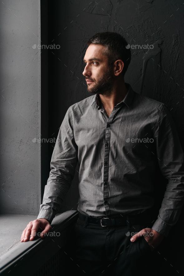 Handsome man standing over dark background - Stock Photo - Images