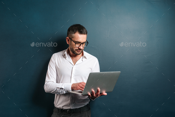 Serious man wearing glasses using laptop computer. - Stock Photo - Images